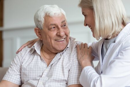 Middle-aged nurse hug elderly man patient sitting on couch look at each other having warm relations understating. Concept of caregiving solve problems together helping give mental or physical support