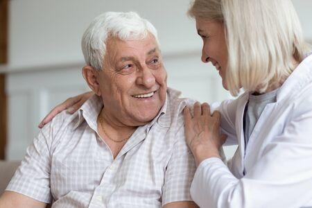 Une infirmière d'âge moyen étreint un patient âgé assis sur un canapé se regardant les uns les autres ayant des relations chaleureuses sous-estimées. Le concept de prestation de soins résout les problèmes ensemble en aidant à apporter un soutien mental ou physique