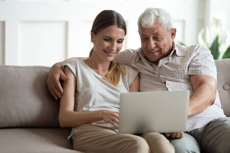 Grandfather adult granddaughter spend time together use laptop, old father hug grown up daughter seated on sofa browse website, younger generation teach explain to older how to use modern tech concept