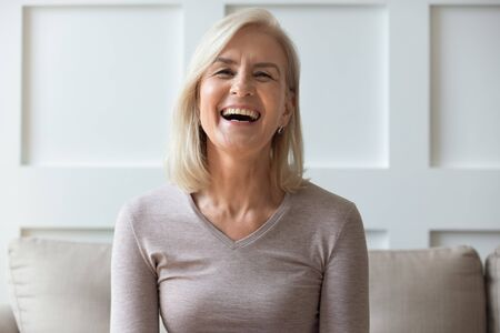 Vivacious elderly 60s blond woman with wide toothy candid smile sit on sofa look at camera head shot portrait, having video call lively positive conversation with friend via online application concept
