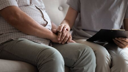 Close up conceptual image nurse holding clipboard and touch hands of patient talking sitting together on couch with elderly man, professional helpful caregiver comforting senior male at nursing home Stock Photo
