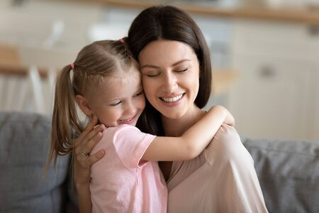 Happy loving mother embracing little daughter close up, enjoying free time together at home, smiling mum and adorable preschool child hugging and cuddling with closed eyes, trusted good relationship