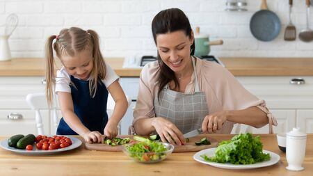 Smiling mother and pretty little daughter wearing aprons cooking salad together in kitchen, caring mum chopping cucumber with knife on cutting board, teaching adorable child girl to cut vegetables