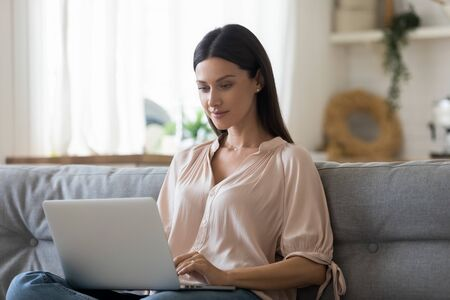 Serious young woman using laptop at home, looking at screen, reading email, watching video or movie, beautiful girl shopping or chatting online in social network, freelancer working on project Stock Photo