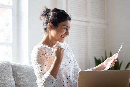 Feliz mujer india leyendo buenas noticias en carta, notificación, sosteniendo papel, niña sonriente regocijándose de éxito, estudiante emocionado por los resultados positivos del examen, mostrando gesto de sí, sentado en el sofá en casa