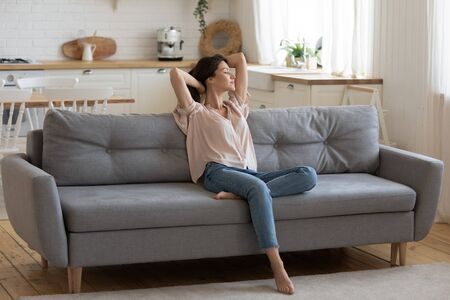 Calm serene young woman relaxing on comfortable couch at home with closed eyes and hands behind head, satisfied girl stretching on sofa, daydreaming and meditating in cozy living room