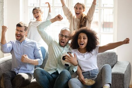 Excited diverse friends watching football match together, celebrating goal, happy fans supporting favorite team, rejoicing victory, screaming with joy, eating popcorn, sitting on couch at home