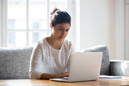 Fokussierte indische Frau, die zu Hause einen Laptop benutzt, auf den Bildschirm schaut, chattet, E-Mails liest oder schreibt, auf der Couch sitzt, ernsthafte Studentin, die Hausaufgaben macht, an einem Forschungsprojekt online arbeitet