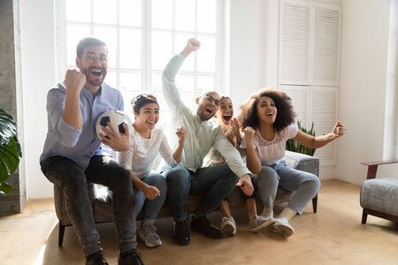 Excited diverse friends watching match on tv together, football fans celebrating victory goal, sitting on couch at home, screaming, supporting favorite soccer team, win sport bet, successful game