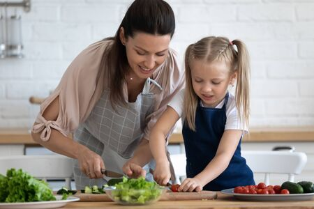 Caring mother teaching little daughter to cook salad in kitchen, young mum and adorable cute girl child wearing apron chopping vegetables with knife on countertop, standing in kitchen at home