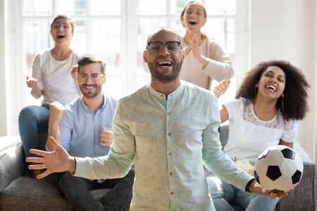 Excited African American man in glasses holding soccer ball, watching match with diverse friends sitting on couch at home, celebrating favorite football team success, goal, screaming with joy