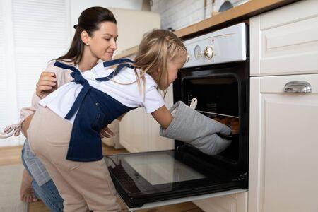 Loving mother teaching little daughter to bake cupcakes in oven, taking out tray, smiling mum and cute adorable child girl wearing aprons cooking muffins, dessert, spending weekend together
