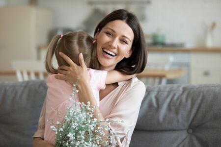 Head shot portrait smiling mother hugging adorable little daughter, thanking for flowers, looking at camera, happy excited mum and preschool child celebrating birthday or women mothers day at home