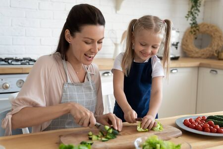Happy mother and cute little daughter wearing apron cooking salad together, having fun, loving mum teaching adorable preschool child to use knife, cut vegetables, standing in kitchen at home