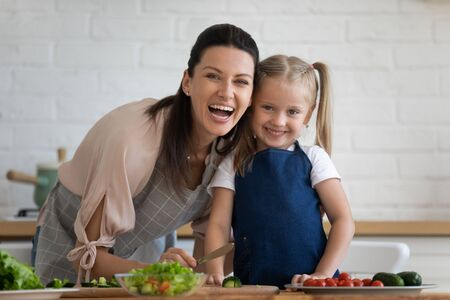 Head shot portrait excited mother and little daughter in kitchen at home, looking at camera, happy mum and adorable cute child wearing aprons cooking salad, chopping vegetables on countertop Stockfoto