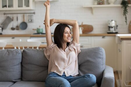 Smiling young woman relaxing, sitting on comfortable couch, stretching hands, looking aside, happy beautiful girl spending weekend at home, dreaming about good future, resting on cozy sofa