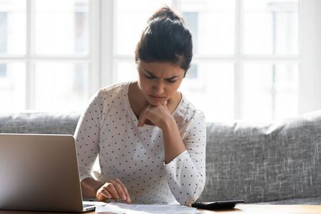 Upset Indian woman reading bad news in paper notification, using laptop, checking loan documents, unhappy female calculating finances, young female student working on difficult project at home Banque d'images