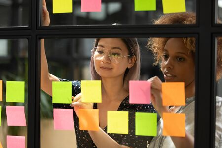 View through glass wall young asian and african female colleagues working together search solution of problem using multicolored bright sticky notes help organize work make brief topics to-do list