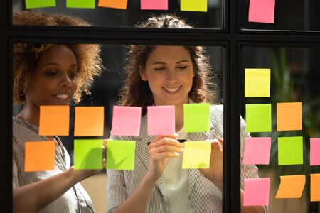 Pretty women colleagues work on project present ideas on post-it sticky notes attached on office glass wall, multiracial girls workers develop startup, brainstorming sharing thoughts. Teamwork concept
