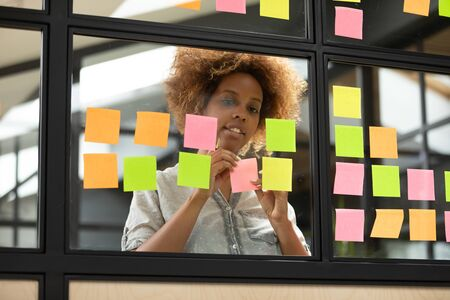 African ethnicity businesswoman putting writing her thoughts on attached on glass window sticky adhesive notes standing in workplace office room, female startupper creates fresh and cool ideas concept Banco de Imagens