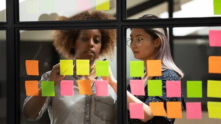 Serious focused asian and african business women standing in office room near glass wall where attached colorful sticky notes writing plan to achieve final goal working together on new project concept