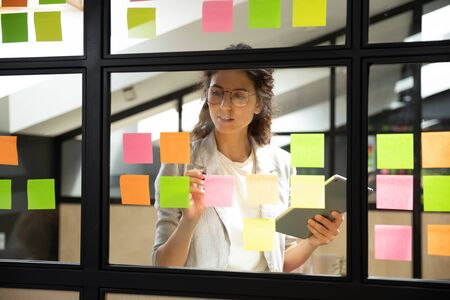 Businesswoman creates priority to-do list standing behind glass wall writes fresh ideas interesting creative thoughts on multicolored  sticky notes using tablet having fruitful workday concept