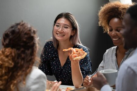 Asian office worker eat pizza together with workmates, multi-racial workers enjoy party celebrate successful deal having fun chatting joking, teambuilding and friendship at work, food delivery concept