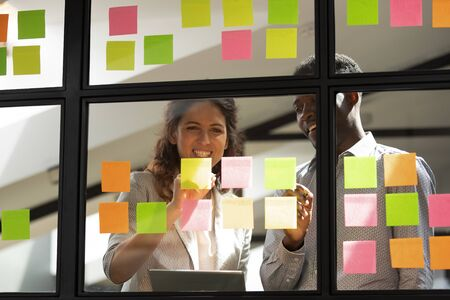 African and caucasian two workmates brainstorming together standing indoors writing new creative thoughts, fresh ideas on colourful sticky notes, reminders to-do list attached on glass wall