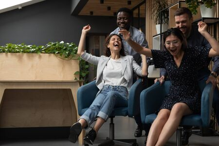 Four diverse office workers riding on chairs raise hands screaming with joy feel speed adrenaline laughing having fun enjoy break resting distracted from boring work, funny activity with mates concept Banco de Imagens