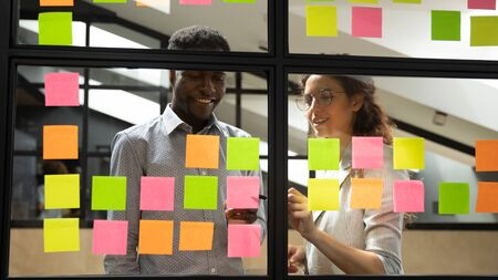 Multiracial colleagues developing business ideas use post-it notes view through glass, mates read written tasks shown on stickers attached on wall, effective way do work dont forget anything concept Banco de Imagens