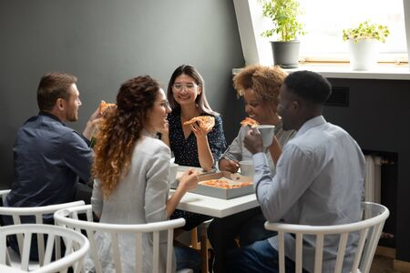 Multi-ethnic colleagues at lunch eat pizza employees seated at table enjoy italian food drink coffee, way to get to know each others better strengthen relationships, teambuilding pause at work concept Banco de Imagens