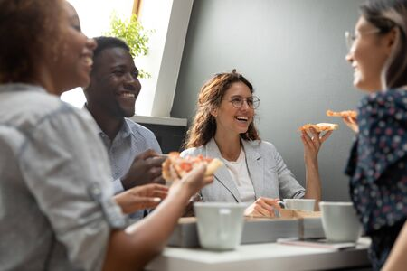 Group of friends multiracial company members having lunch during break at workplace eating pizza chatting laughing enjoy communication, team building activity and good warm relations at work concept