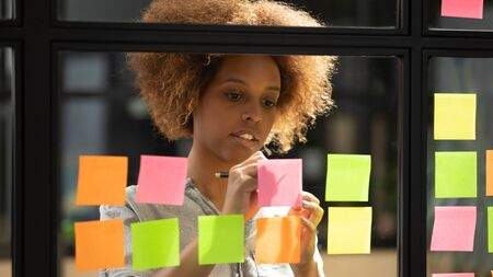 African young woman office worker writing down on sticky notes, managing to-do list, create strategy plan or fresh business startup ideas view through glass wall, brain work and productivity concept