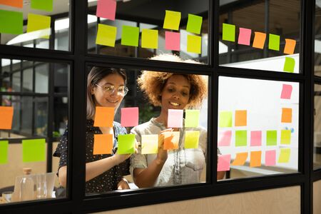 Multi-ethnic women associates enjoy process of plan creation startup fresh innovative ideas feels inspiration writing down on sticky notes, reminders to-do list attached on glass wall in modern office Banco de Imagens