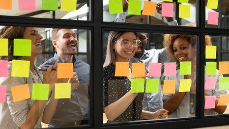Colorful sticky notes attached on glass wall, group of multi-ethnic business people feels happy celebrating successful accomplishment of project cool startup ideas, found solution of challenge concept
