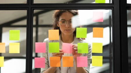 Attractive concentrated business lady in glasses creating to-do list using multi coloured sticky notes attaching them to transparent wall standing behind glass view, be more productive concept Banco de Imagens