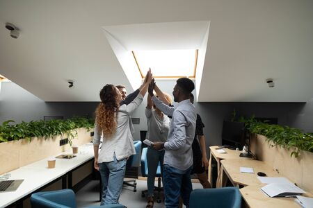 Different ethnicity millennial office workers staff members celebrating success at common business standing in shared open space giving high five feeling excitement concept of team building and spirit.