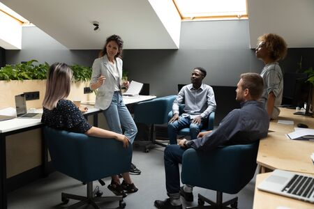 Attractive caucasian female team leader explain project strategy talking to multi-ethnic company members express opinion or share creative ideas during corporate informal meeting in co-working office.