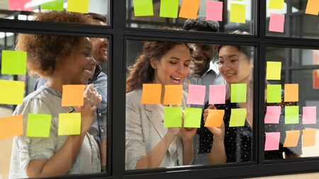 Positive multi-ethnic group of business people working together on new project writing main topics sharing creative ideas thoughts using colourful sticky notes, concept of synergy and teamwork