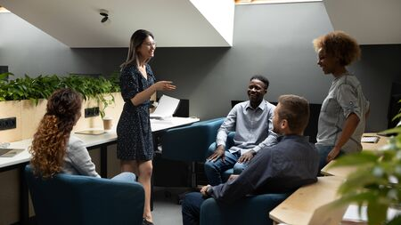 Diverse staff gathered together in co-working listen speech of asian ethnicity mate, multi racial department during break interacting having informal positive conversation, friendly relations concept