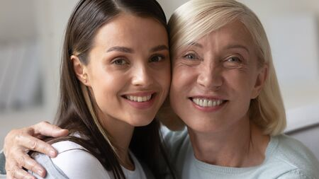 Head shot close up portrait of happy mature lady bonding with attractive grown up daughter. Smiling two generations, attractive young woman embracing hugging elder beautiful mother, looking at camera. 版權商用圖片