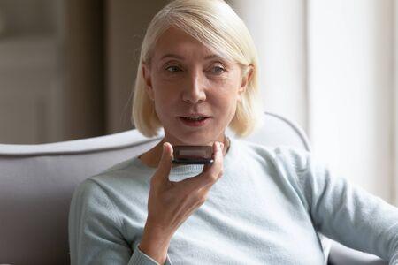 Disparo a la cabeza de cerca retrato mujer rubia jubilada con asistente virtual en el teléfono móvil, sentado en casa. Feliz abuela de 60 años grabando mensajes de voz en las redes sociales en el teléfono inteligente.