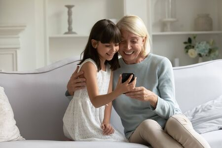 Overjoyed mature grandmother cuddling little granddaughter, watching funny video together on smartphone, sitting on comfortable couch at home. Happy girl with granny holding video call on cellphone.