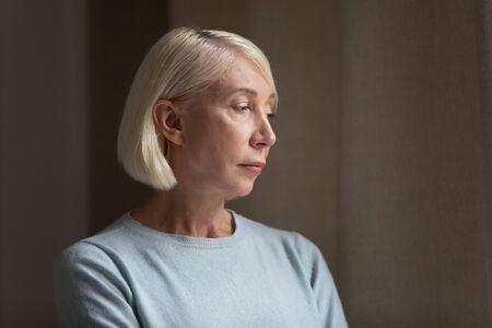 Zijaanzicht hoofd geschoten close-up portret verdrietig boos volwassen verloren in gedachten dame eenzaam voelen. Gestresste peinzende oudere vrouw die denkt aan gezondheidsproblemen, slechte diagnose, familieproblemen, wegkijken. Stockfoto