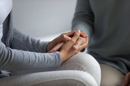 Close up caring young woman holding hand of elder mother, demonstrating support and love. Best friends, relative people, middle aged mother and grown up daughter having sincere conversation together. 免版税图像