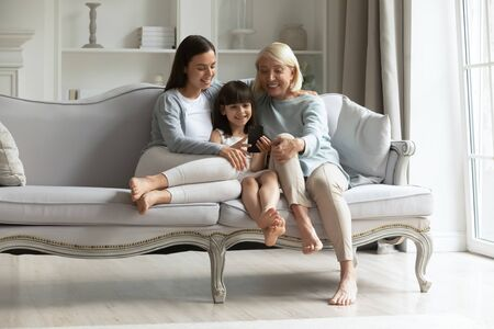 Full length happy 3 generations family sitting together on couch in living room, watching funny cartoons, recording video, taking selfie. Smiling little girl enjoying free time with mommy and grandma. Stok Fotoğraf