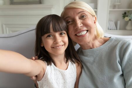 Mobile camera view smiling little adorable preschool girl taking selfie shot photo with smiling middle aged grandmother, sitting on sofa at home. Happy family bloggers recording funny video together. Stok Fotoğraf