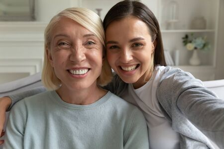 Head shot close up portrait happy millennial grown up daughter taking selfie photo with middle aged smiling mother, sitting together at home. Overjoyed family of two recording video or making call. Stok Fotoğraf - 132144195