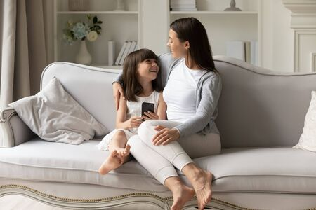 Overjoyed small girl sitting with happy mommy on comfortable couch, having fun together, communicating, using smartphone, discussing mobile language learning mobile app, recording funny video at home. Stok Fotoğraf