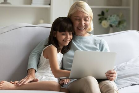 Smiling older woman hugging happy little adorable granddaughter, using computer together, sitting on cozy sofa in living room. Involved small girl with granny shopping, watching funny movie on laptop.